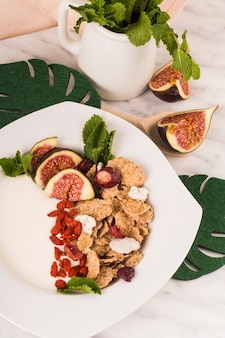 偽の葉の近くのプレート上の健康的な朝食とミントの瓶の葉