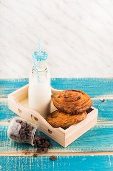 木製の表面上のチョコレートチップの瓶の近くにトレイの渦巻きペストリーとミルクボトル