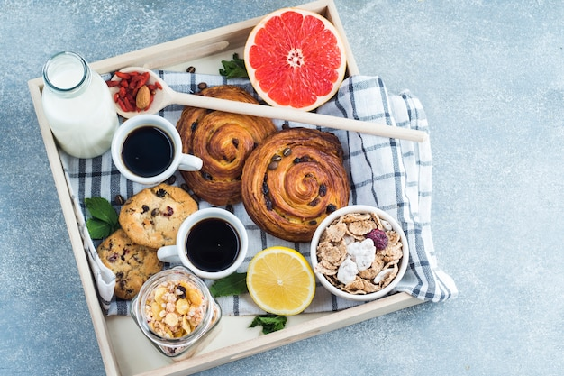 コンクリートの背景に対する健康的な朝食の木製トレイ