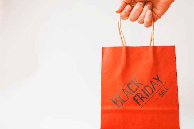 赤いショッピングバッグで手