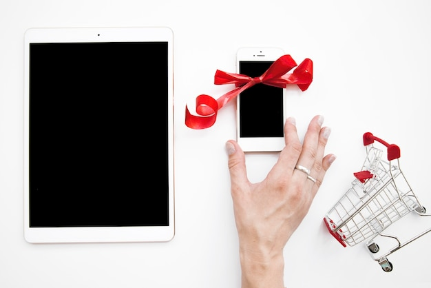 スマートフォンでタブレットとショッピングトロリーの近くにいる女性の手