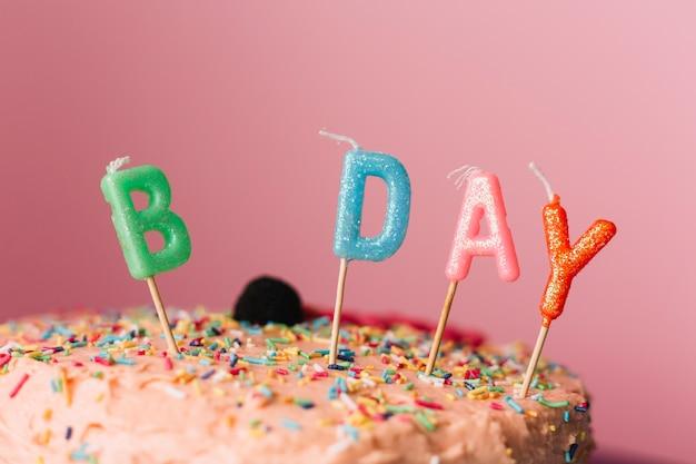 色とりどりの背景にケーキの誕生日のろうそく