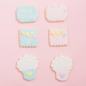 ピンクの背景に配置された様々なジンジャーブレッドアイシングクッキー