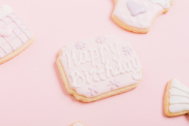白い背景の上に幸せな誕生日のテキストを持つクリーム色のクッキー