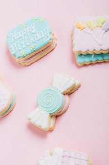 ピンクの背景を覆う様々な新鮮なクッキー