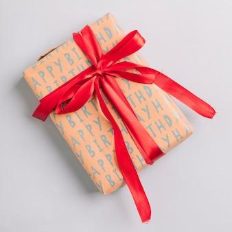 白い背景に幸せな誕生日プレゼントとして赤いリボンとラップされたギフトボックス