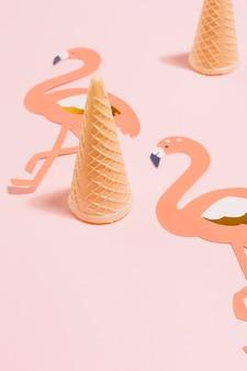 ピンクの背景に切り取られたフラミンゴの紙とワッフルアイスクリームコーン