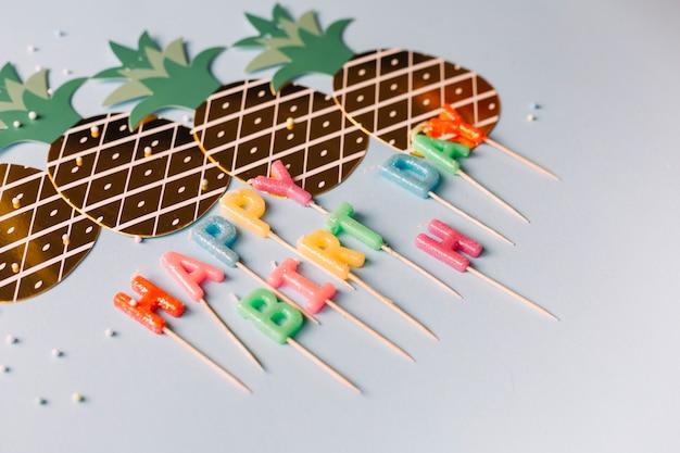 白い背景にカラフルな誕生日の蝋燭と切り取ったパイナップルの形