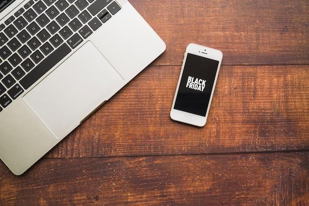 木製ボード上のラップトップに近いスマートフォン