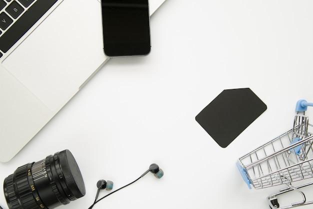 Ноутбук рядом с смартфоном, цифровыми устройствами и торговой тележкой