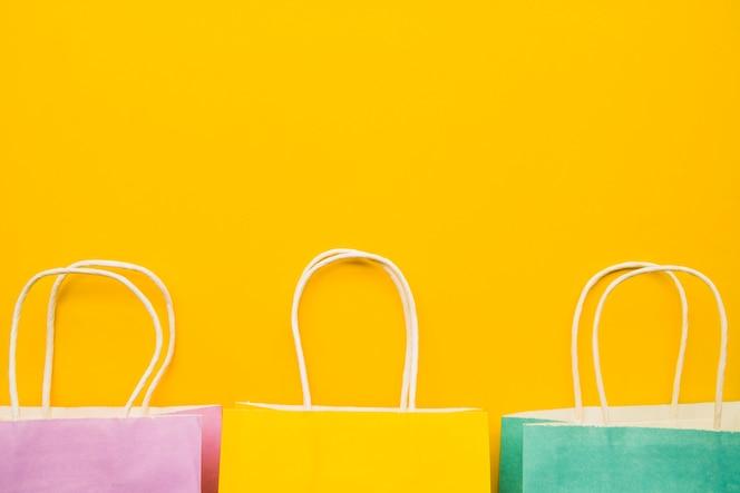 黄色のテーブルにカラフルなショッピングバッグ