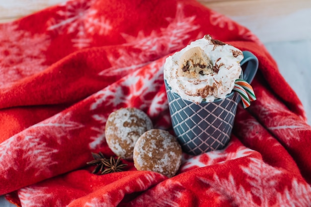 毛布にホイップクリーム入りコーヒーのカップ