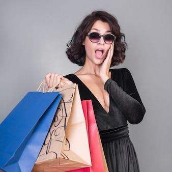 ショッピングパケットを持つ驚いた女性
