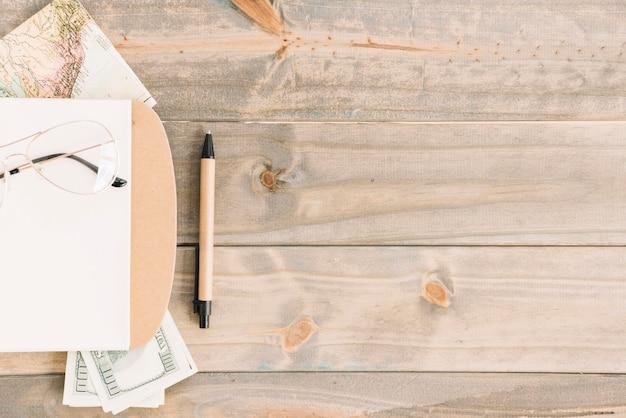 眼鏡;メモ帳。通貨;地図とペン、木製の板張りの背景