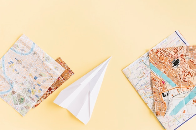 Разнообразие карт с белой бумаги самолет на бежевом фоне