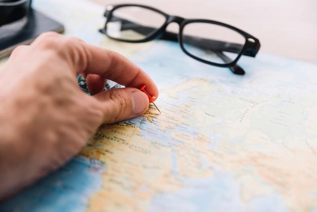 ぼかし地図上にプッシュピンを持っている人の手のクローズアップ