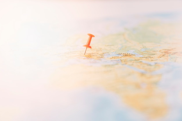 Красная канцелярская кнопка, отмечающая местоположение на карте мира