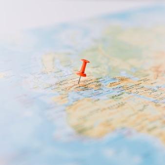 デフォーカスされた世界地図上の赤い親指のタックのクローズアップ