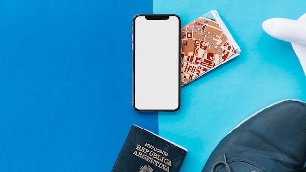 白い画面の表示スマートフォン;地図;パスポート;おもちゃの飛行機と靴を明るく暗い背景に