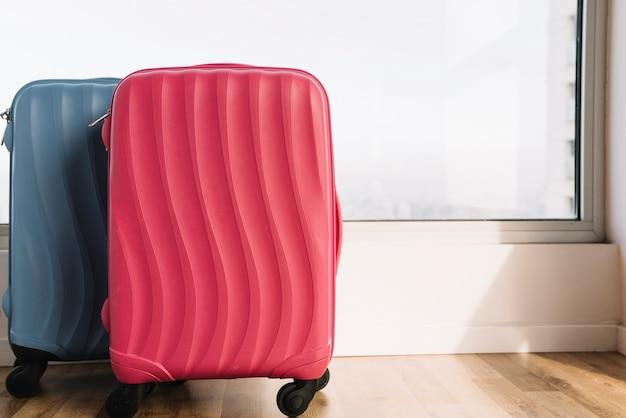 木製の床の窓の近くの荷物のスーツケース