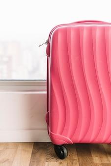 Крупный план розовый дорожная сумка с колесами на деревянном полу возле окна