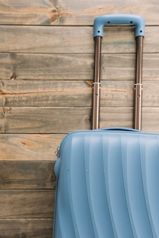 Реалистичный пластиковый чемодан из поликарбоната с ручкой на деревянном фоне