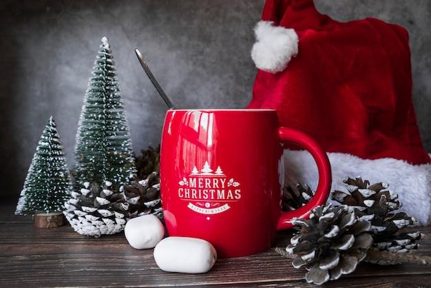 クリスマスの帽子と小さなモミの近くの赤いマグカップ