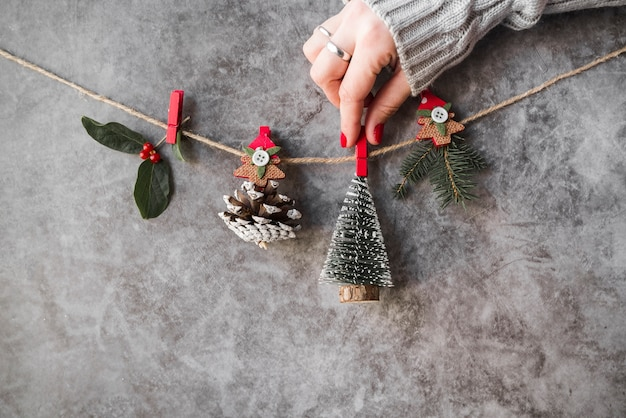 手はクリスマスの装飾を糸に固定する