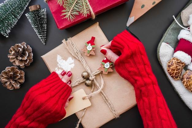 Женщина, держащая подарочную коробку на столе
