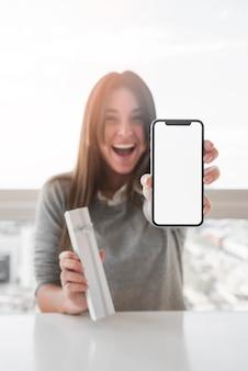 スマートフォンを示す幸せな女性