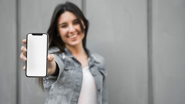 Улыбается молодая женщина, показывая смартфон