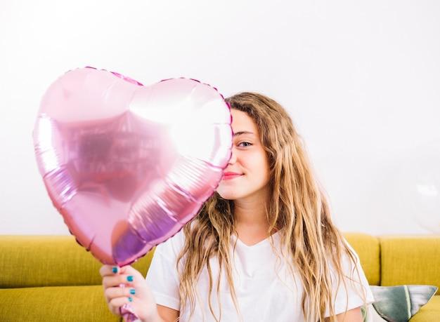 金属風船を持つ誕生日の女の子