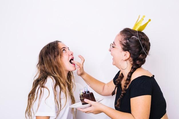 彼女の友人にチョコレートケーキを与えるティーンエイジャー