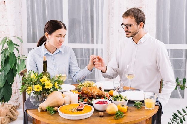 お祝いのテーブルで手を持っているカップル