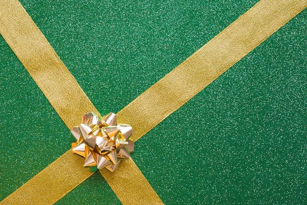 Золотой лук и ленты на зеленом фоне