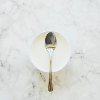 テーブルの上に白いボウルのスプーン