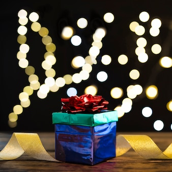 デフォーカスされたライトの近くのプレゼントとリボンのスタック