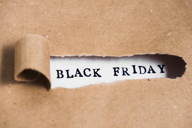 Черная пятничная надпись между бумагой ремесла