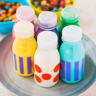 Цветные бутылки молока на тарелке