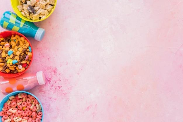 Чаши зерновых с молочными бутылками на розовом столе