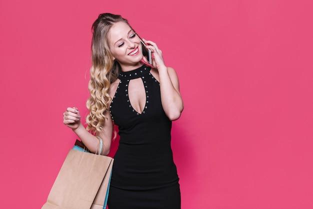 電話で話すバッグを持つ陽気な女性