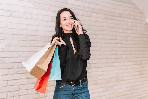 電話で話すバッグ付きの現代的な買い物客