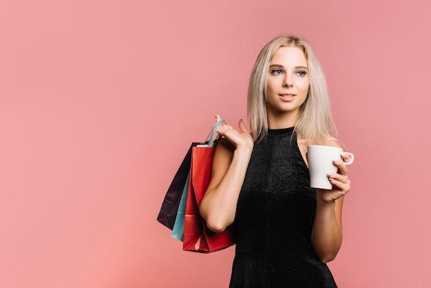 バッグとカップを持つ女性