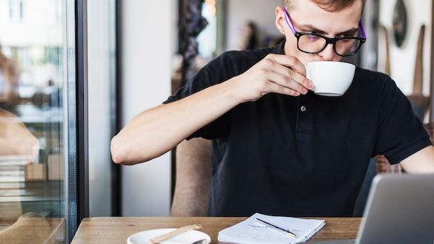 ラップトップでテーブルでコーヒーを飲む男