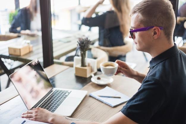ラップトップで木製のテーブルでコーヒーを飲む男
