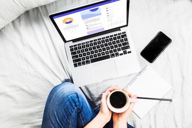 Человек на кровати с чашкой кофе и ноутбуком