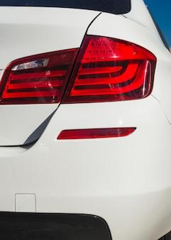 Задняя часть матового белого автомобиля с задним освещением
