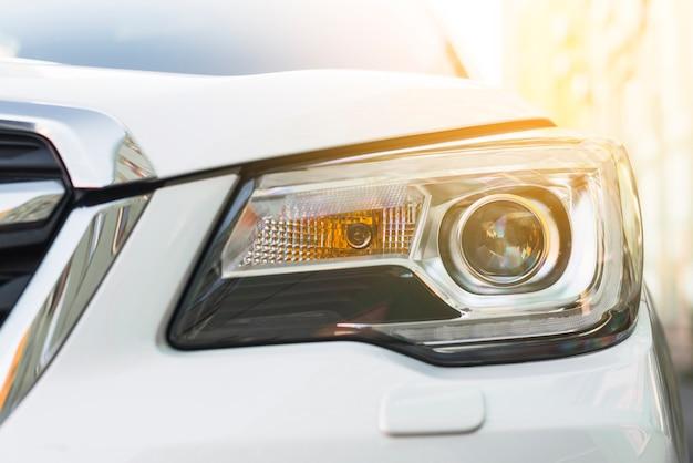 白い自動車のモダンなヘッドライト