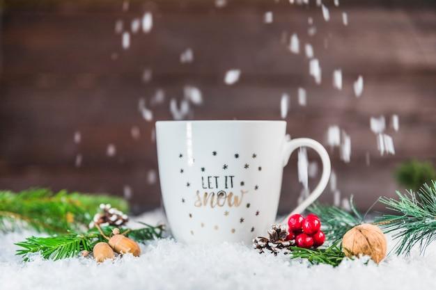 雪の上で枝や枝の近くのカップ