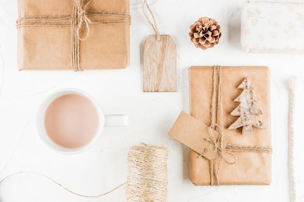 Подарочные коробки рядом с чашкой, ловушкой, тегами и резьбой